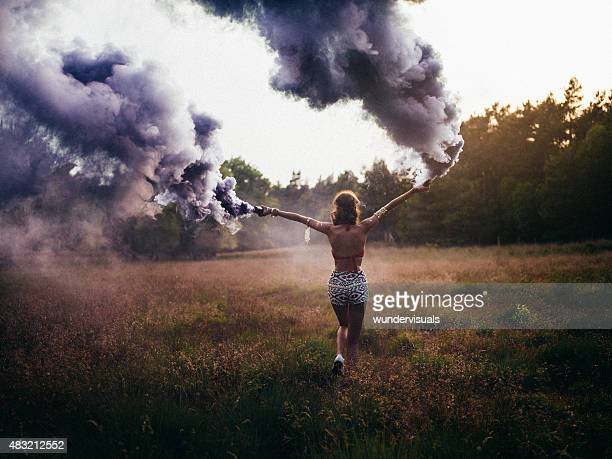 hippie girl running through field with purple smoke flares - opstand stockfoto's en -beelden