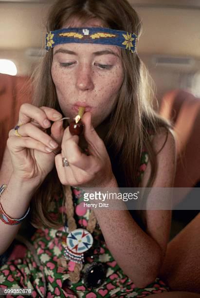 Hippie girl smokes marijuana with a little pipe on the Monkees tour plane