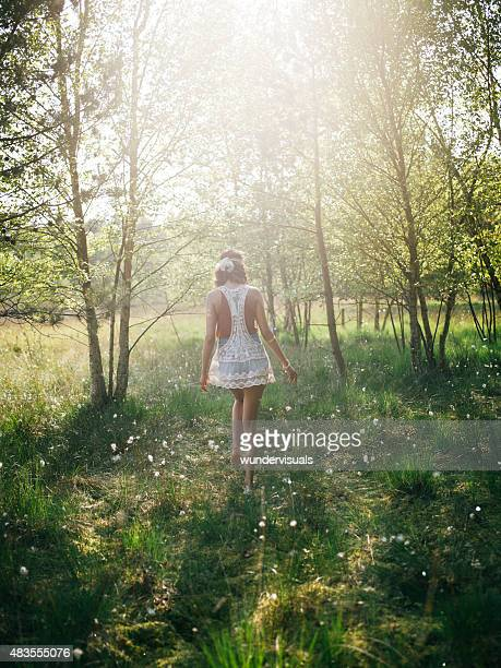 Hippie girl walking through a summer park with trees