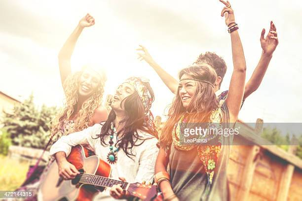 Hippie group playing guitar and dancing together