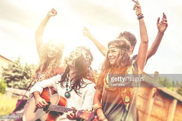 Hippie-Gruppe spielt Gitarre und Tanzen zusammen