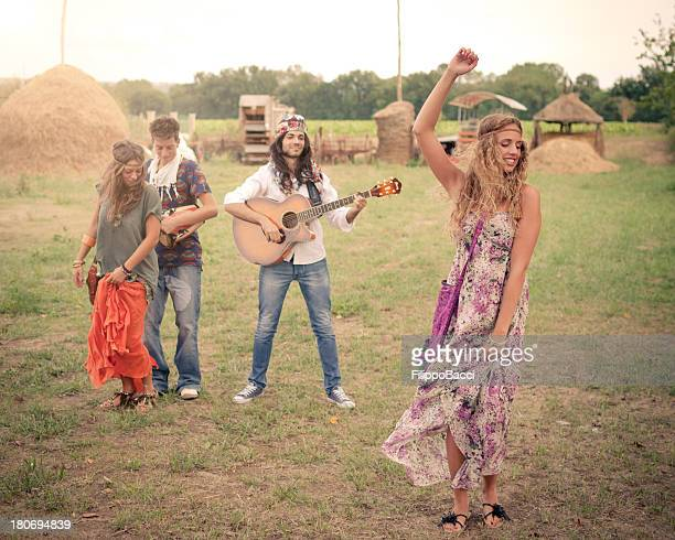 Hippie group singing and dancing in a field
