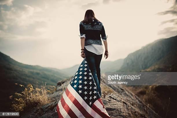 Hippie holding US flag on mountain