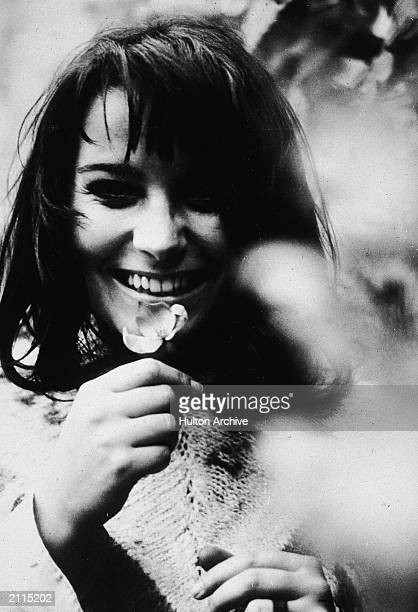 A hippie laughs while holding a flower in the Haight Ashbury section of San Francisco California c 1969
