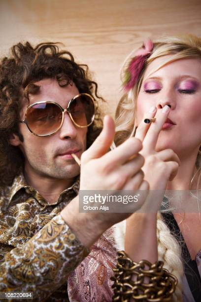 Hippie Man and Young Woman Smoking Marijuana Cigarette