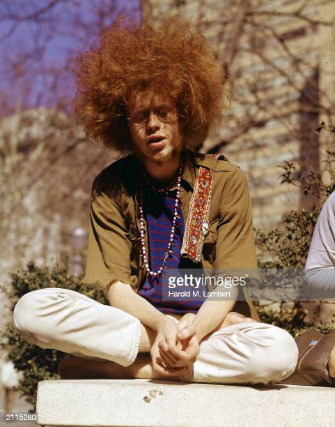 A hippie with a large Afrolike hairstyle sitting crosslegged outdoors 1960s He wears a beaded necklace and a shirt with torn sleeves