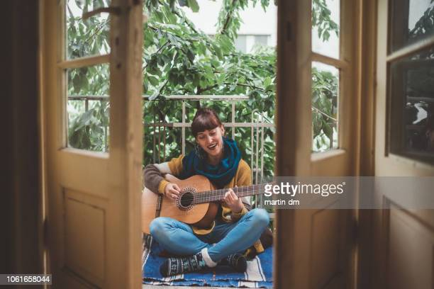 hippie woman playing the guitar at home - balcony stock pictures, royalty-free photos & images