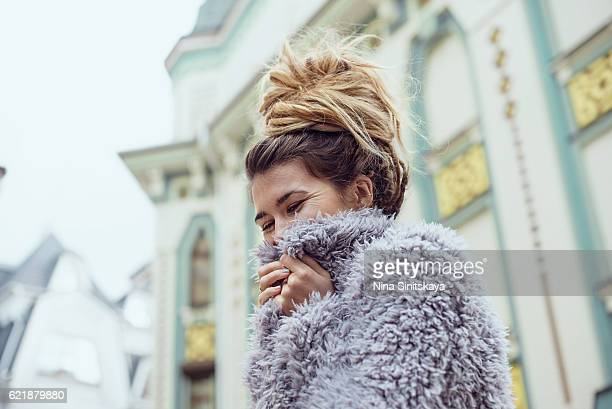 hippie woman wrapping up in fake fur coat outdoors - hair bun stock pictures, royalty-free photos & images