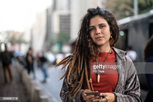 hippie young woman using her smartphone in the city - alternative lifestyle stock pictures, royalty-free photos & images