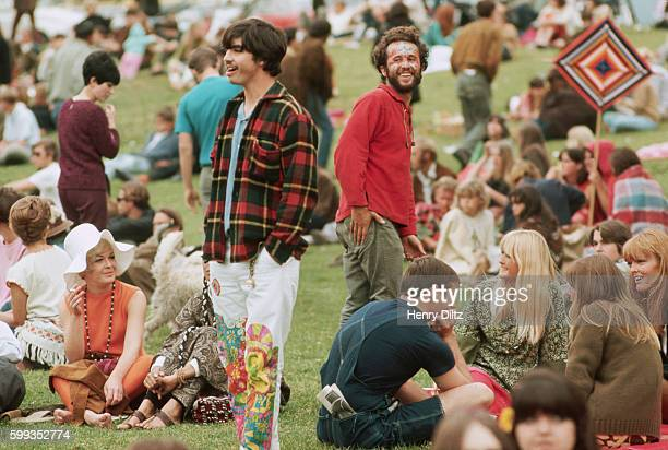 Hippies crowd a park for a lovein Two socialites sit in the midst to check out the scene