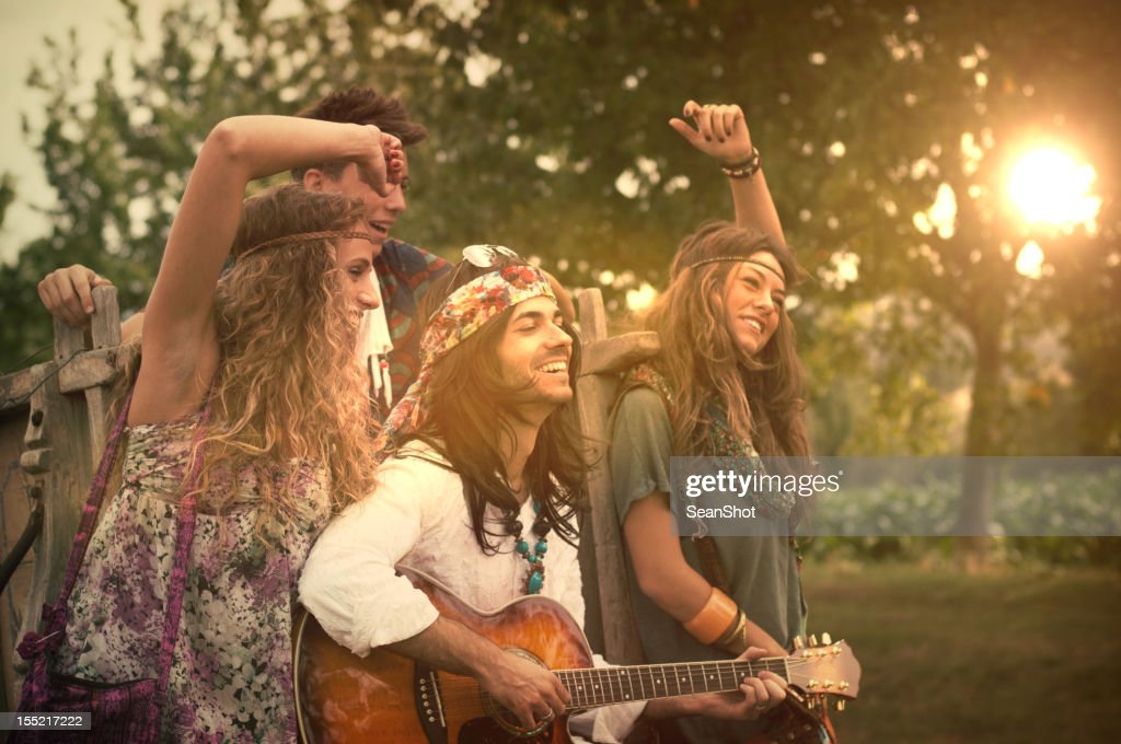 hippies dancing and playing guitar 1970s style stock photo