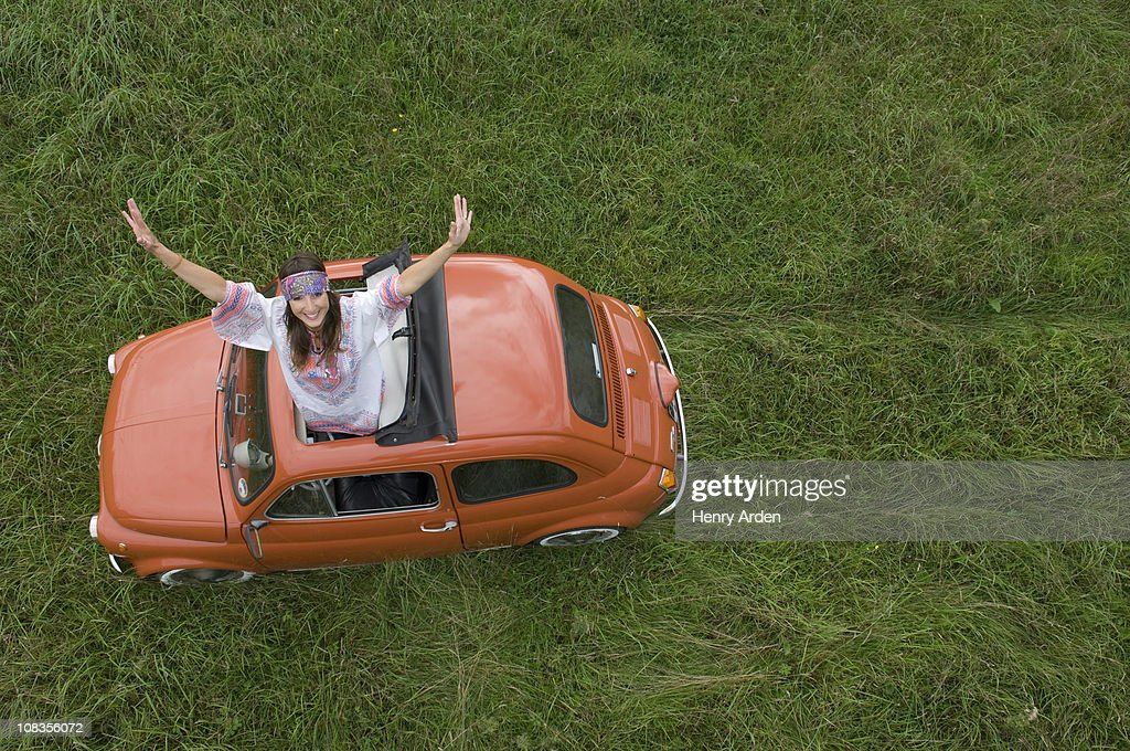 Hippy female stretching out of car : Stock Photo