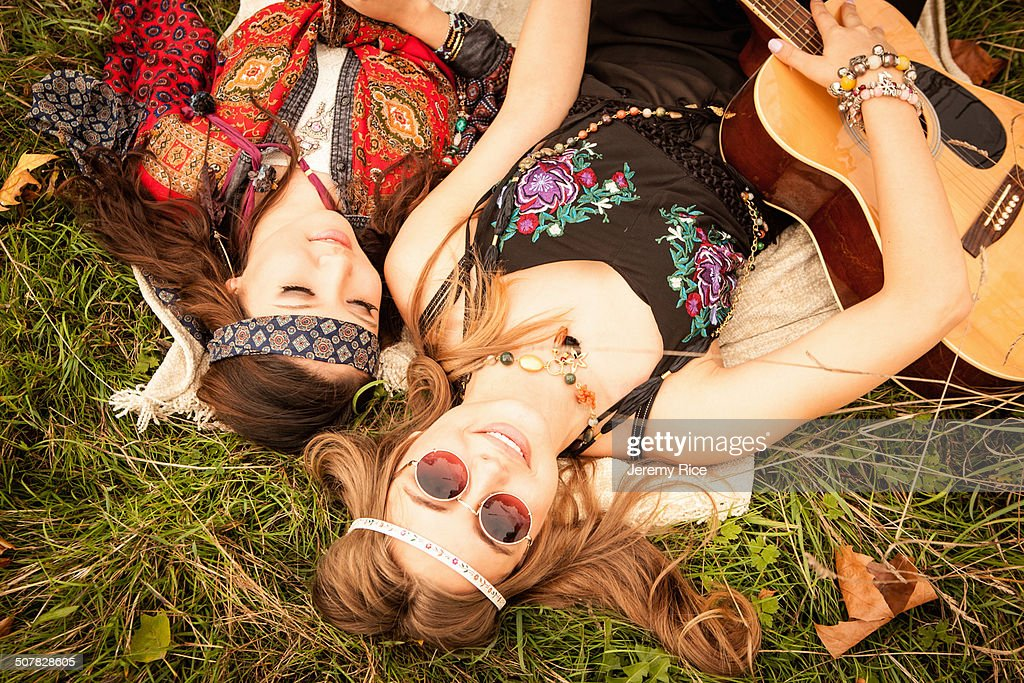 Hippy girls lying in field with guitar : Stock Photo