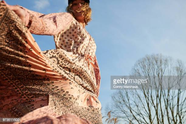 hippy style woman dancing against blue sky, low angle view - long dress stock pictures, royalty-free photos & images