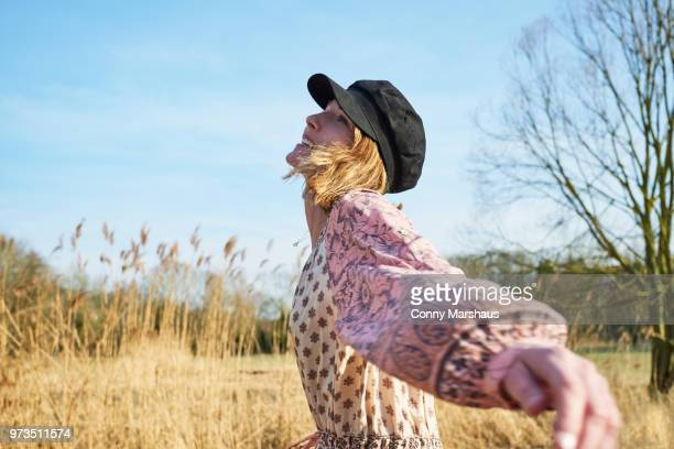 hippy style woman dancing among reeds - robe longue photos et images de collection