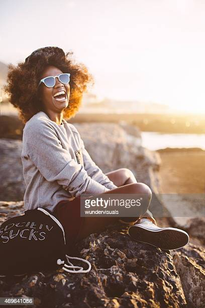 Hipster Afro teen girl laughing on the beach at sunset