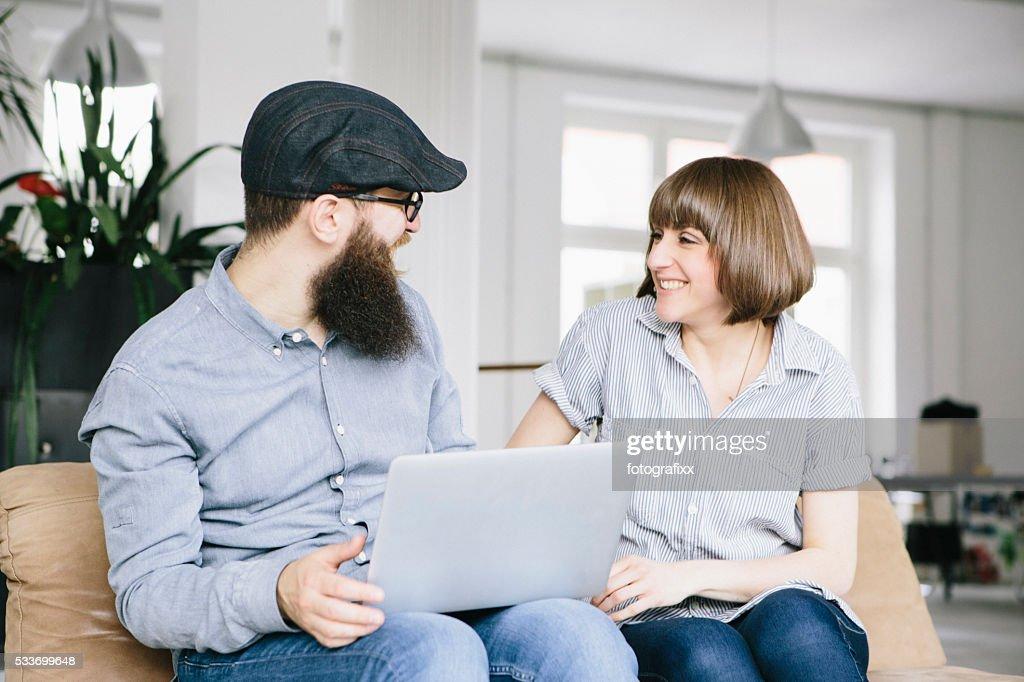 Slip a vita bassa e ragazza sedersi sul divano e lavorano al computer portatile : Foto stock