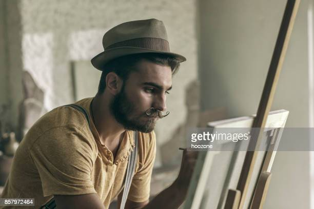 hipster artist painting in an atelier stock photo getty images