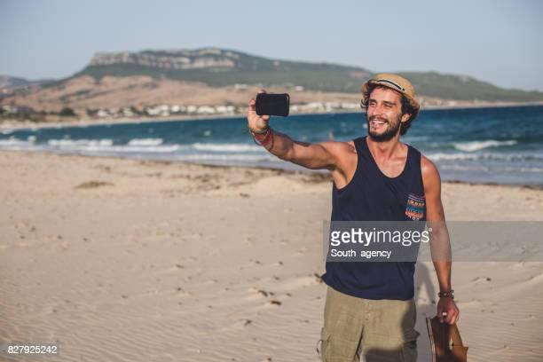 Hipster en la playa haciendo selfie