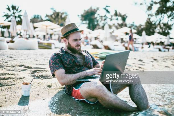 hipster author is writing poetry on laptop at the beach - poet stock pictures, royalty-free photos & images