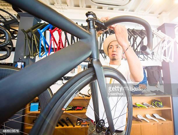 Hipster bike technician adjusting handlebars