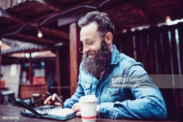 Homme d'affaires de hipster calcul des Profits financiers tout en buvant du café au Bar