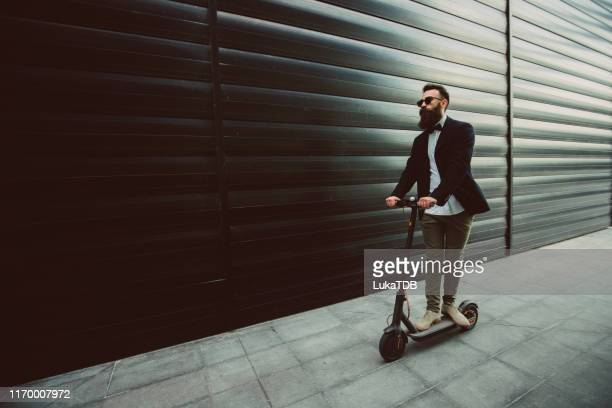 hipster businessman riding a scooter in the city - electric scooter stock pictures, royalty-free photos & images