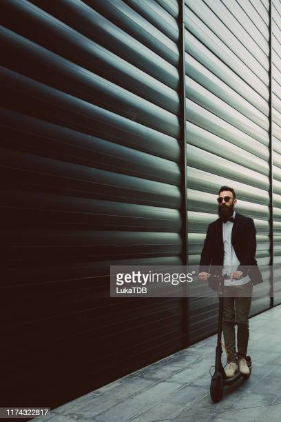 hipster businessman riding a scooter in the city - one man only stock pictures, royalty-free photos & images
