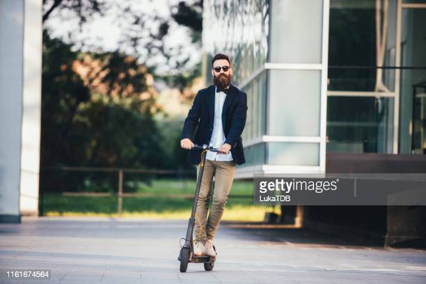 hipster businessman taking an electric scooter to work - electric scooter stock pictures, royalty-free photos & images