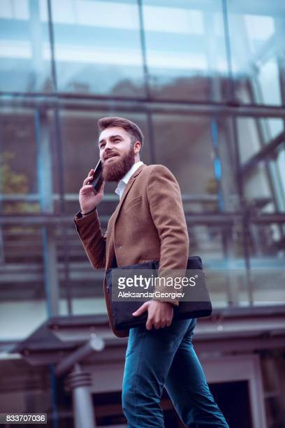 Hipster Businessman with Laptop Bag Talking on Mobile Phone at City Street