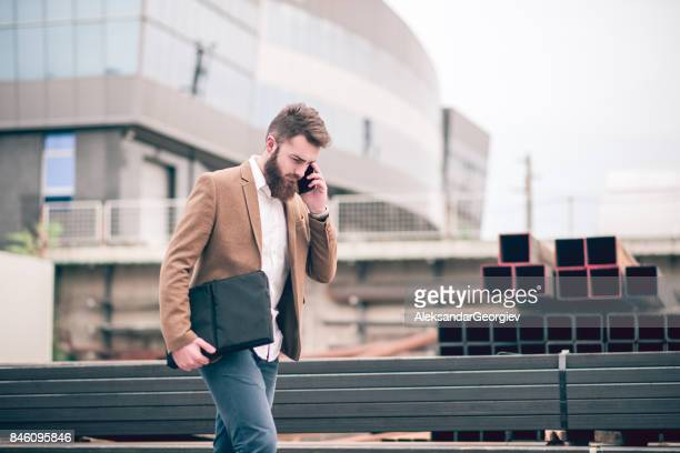 hipster businessman with laptop bag talking on mobile phone at the store warehouse - briefcase stock photos and pictures