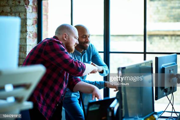 hipster businessmen fist bumping in modern office - creative director stock pictures, royalty-free photos & images