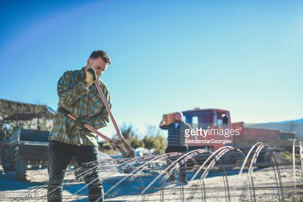 Hipster Construction Worker Cutting Steel Bars