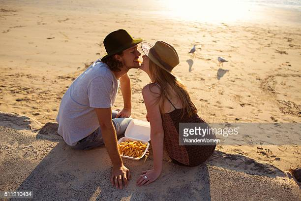 Hipster couple feeding eachother chips on Australian beach at sunset