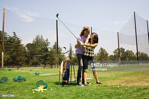 Hipster couple golfing