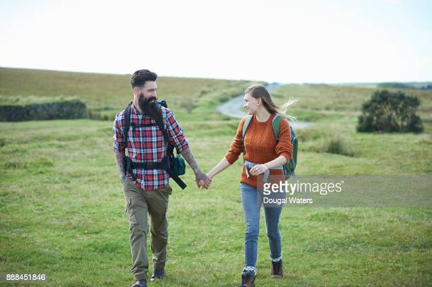 Hipster couple hiking on moorland holding hands.