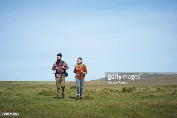 Hipster couple hiking on moorland, UK.