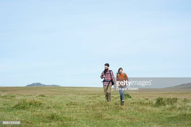 Hipster couple hiking on southern England moorland.