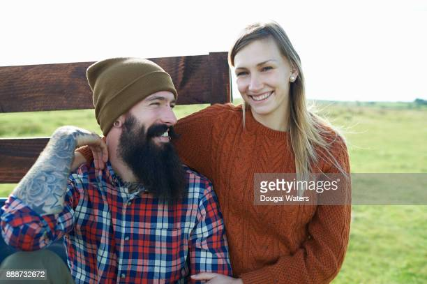Hipster couple laughing together on road trip.