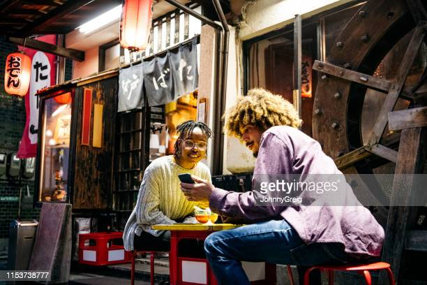 hipster couple looking at smartphone outside restaurant - tourist stock pictures, royalty-free photos & images