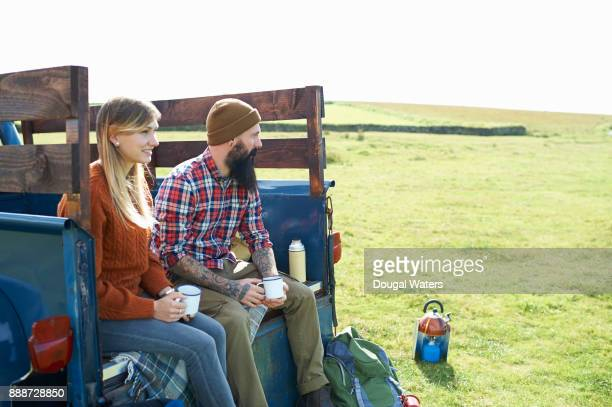 Hipster couple on hiking road trip take a break.