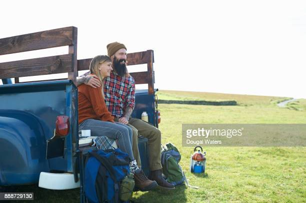 Hipster couple on hiking road trip together with vintage pickup truck.