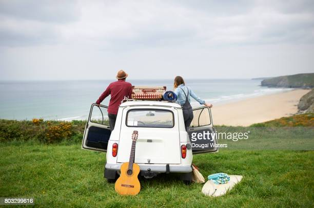 Hipster couple on road trip overlooking sea.