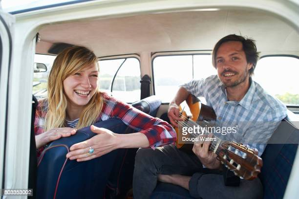 Hipster couple on road trip playing guitar in car.
