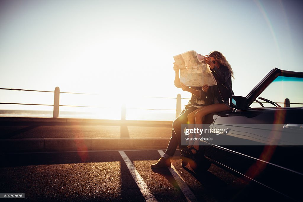 Hipster couple planning their summer seaside road trip with convertible : Stock Photo