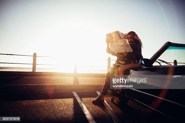 Hipster par de verano en la playa de su viaje a convertible