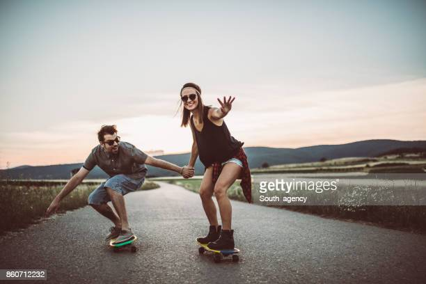 Hipster couple skateboarding
