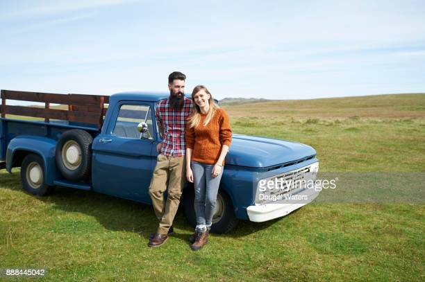 Hipster couple standing beside vintage truck in countryside.