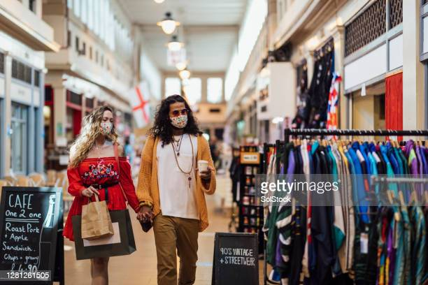 hipster couple walking through a market wearing protective face masks - buying stock pictures, royalty-free photos & images