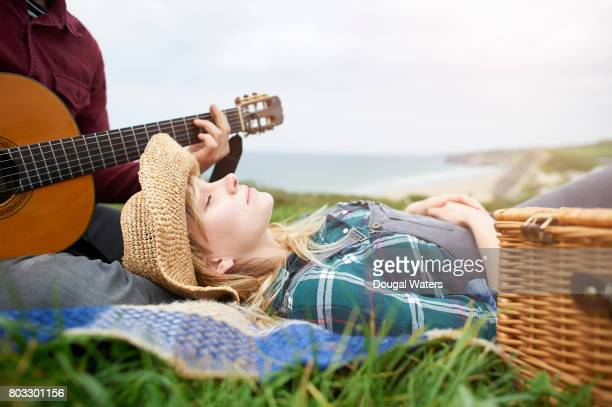 Hipster couple with guitar and picnic beside sea.